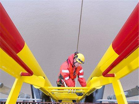 Offshore windfarm worker climbing turbine, high angle view Stock Photo - Premium Royalty-Free, Code: 649-08086419