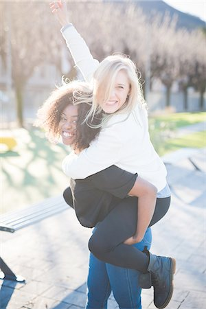 Two female friends giving piggy backs in park Stock Photo - Premium Royalty-Free, Code: 649-08086413