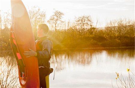Young man holding kayak by lake Stock Photo - Premium Royalty-Free, Code: 649-08086650