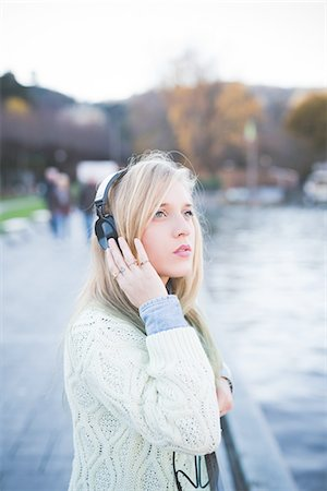 Young woman looking up whilst listening to headphones on lakeside, Como, Italy Stock Photo - Premium Royalty-Free, Code: 649-08086817