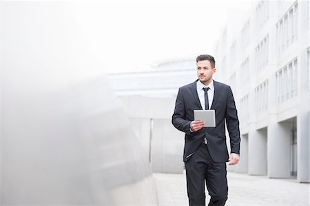 Suited young businessman walking with digital tablet outside office Stock Photo - Premium Royalty-Free, Code: 649-08086868