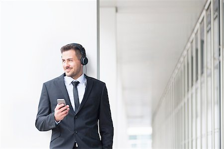 Young businessman outside office listening to smartphone music on headphones Stock Photo - Premium Royalty-Free, Code: 649-08086871