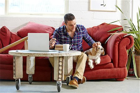 Mid adult man writing address on parcels whilst petting dog in picture framers Stock Photo - Premium Royalty-Free, Code: 649-08086938