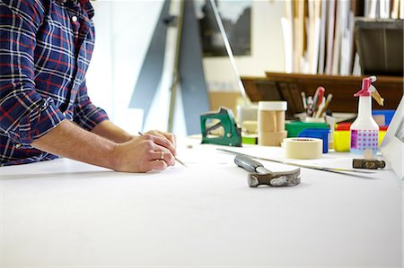 Mid adult man writing measurement on workbench in picture framers workshop Stock Photo - Premium Royalty-Free, Code: 649-08086958