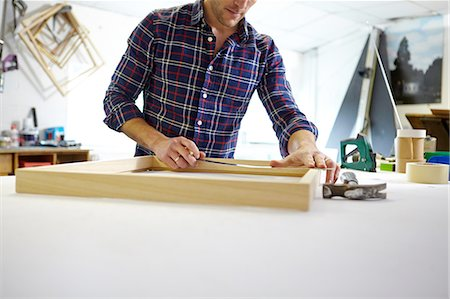 Mid adult man measuring frame on workbench in picture framers workshop Stock Photo - Premium Royalty-Free, Code: 649-08086959