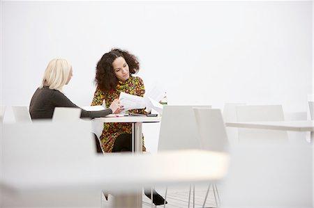 Two businesswomen checking paperwork at office meeting Stock Photo - Premium Royalty-Free, Code: 649-08117826