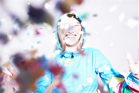 Studio shot of young woman scattering confetti Stock Photo - Premium Royalty-Free, Code: 649-08117849