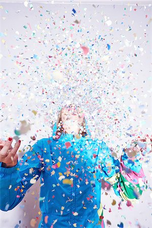 Studio shot of young woman and explosion of confetti Stock Photo - Premium Royalty-Free, Code: 649-08117841
