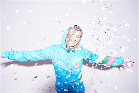 Studio portrait of young woman throwing confetti Stock Photo - Premium Royalty-Free, Code: 649-08117851