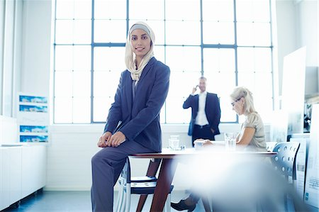 Portrait of young businesswoman sitting on office desk Foto de stock - Sin royalties Premium, Código: 649-08117891