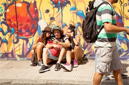 Three young adult hipsters sitting on sidewalk reading smartphone texts, Rio De Janeiro, Brazil Stock Photo - Premium Royalty-Free, Code: 649-08117936