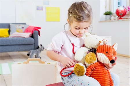 female doctor - Girl playing doctor to soft toys Stock Photo - Premium Royalty-Free, Code: 649-08118149