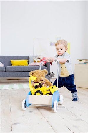 Boy pushing cart of toys at home Stock Photo - Premium Royalty-Free, Code: 649-08118143