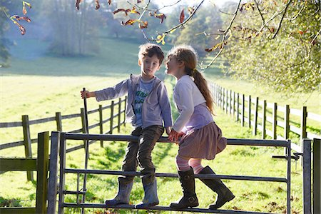 Girl whispering to twin brother whilst climbing over footpath gate Stock Photo - Premium Royalty-Free, Code: 649-08118382