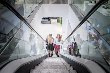 shopping mall - Two female friends moving up escalator in shopping mall Stock Photo - Premium Royalty-Free, Code: 649-08118434