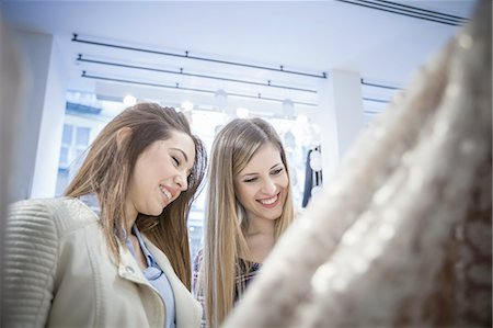 Two female friends shopping for dresses in boutique Stock Photo - Premium Royalty-Free, Code: 649-08118431