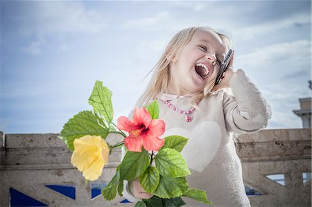 Young girl with flowers laughing and chatting on smartphone, Cagliari, Sardinia, Italy Stock Photo - Premium Royalty-Free, Code: 649-08118450