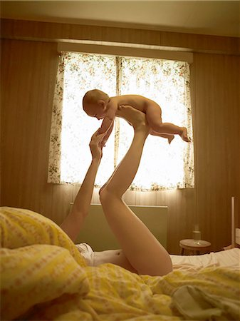 Mother lying on bed balancing baby son on feet Stock Photo - Premium Royalty-Free, Code: 649-08118470