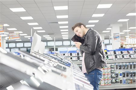 Young male shopper holding up chosen digital tablet in electronics store Stock Photo - Premium Royalty-Free, Code: 649-08118535