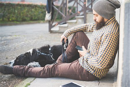 pet - Mid adult man sitting outdoors with dog, using smartphone Stock Photo - Premium Royalty-Free, Code: 649-08118581