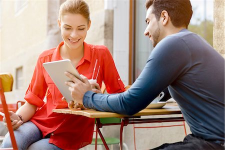 Young man and woman sitting outside cafe, looking at digital tablet Stock Photo - Premium Royalty-Free, Code: 649-08118640