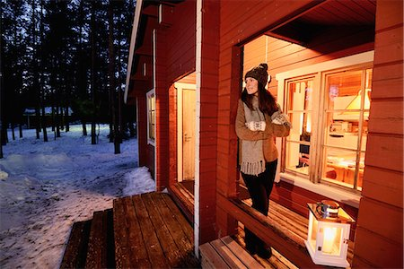 Portrait of young woman looking out from cabin porch at night, Posio, Lapland, Finland Stock Photo - Premium Royalty-Free, Code: 649-08118777