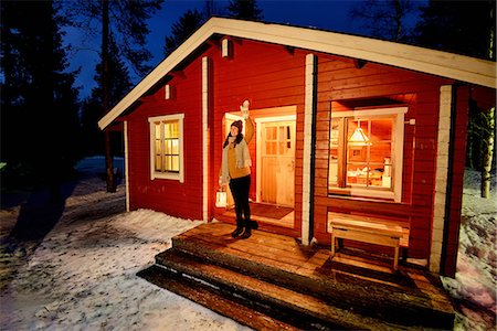 Young woman looking out from cabin porch at night, Posio, Lapland, Finland Stock Photo - Premium Royalty-Free, Code: 649-08118778