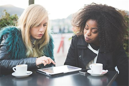 furry - Two young women using touchscreen on digital tablet at sidewalk cafe, Lake Como, Como, Italy Stock Photo - Premium Royalty-Free, Code: 649-08118799