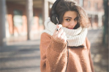 style - Young woman holding up headphone cable on street Stock Photo - Premium Royalty-Free, Code: 649-08118811