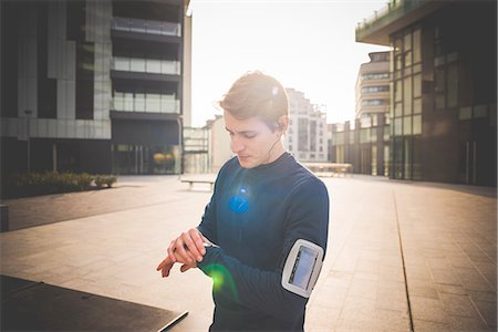 physical fitness - Young male runner checking wrist watch in city square Stock Photo - Premium Royalty-Free, Code: 649-08118831