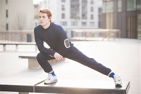 physical fitness - Young male runner stretching in city square Stock Photo - Premium Royalty-Free, Code: 649-08118842