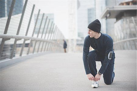 sports - Young male runner fastening trainer lace on city footbridge Stock Photo - Premium Royalty-Free, Code: 649-08118858