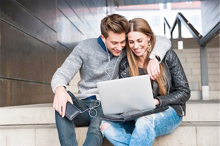 Young couple sitting on stairs using laptop Stock Photo - Premium Royalty-Free, Code: 649-08119143