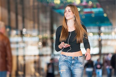 people on mall - Young woman listening to smartphone music whilst strolling in shopping mall Stock Photo - Premium Royalty-Free, Code: 649-08119288