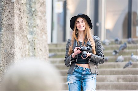 Young stylish woman photographing on city steps with SLR camera Stock Photo - Premium Royalty-Free, Code: 649-08119289