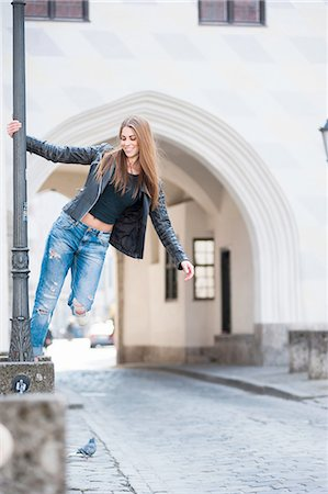street - Young woman swinging on city lamp post Stock Photo - Premium Royalty-Free, Code: 649-08119293