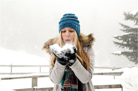 Young woman blowing handful of snow Stock Photo - Premium Royalty-Free, Code: 649-08124907