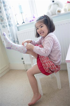 pulling - Young girl sitting on chair, pulling sock on Stock Photo - Premium Royalty-Free, Code: 649-08125100