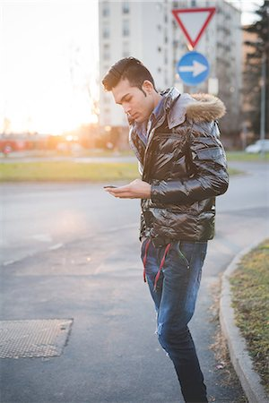 style - Young man using smartphone in the street, Milan, Italy Stock Photo - Premium Royalty-Free, Code: 649-08125128