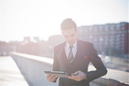 Young businessman using digital tablet on rooftop Stock Photo - Premium Royalty-Free, Code: 649-08125121
