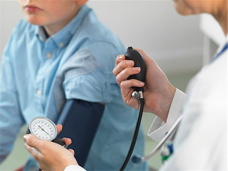 equipment - Doctor reading blood pressure of young boy in clinic Stock Photo - Premium Royalty-Free, Code: 649-08125159