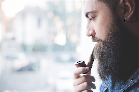 Young bearded man smoking pipe by window Stock Photo - Premium Royalty-Free, Code: 649-08125276