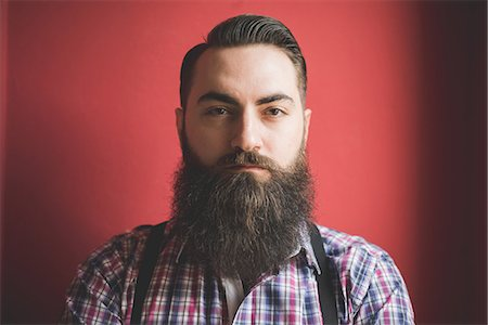 Portrait of young bearded man, red background Stock Photo - Premium Royalty-Free, Code: 649-08125288