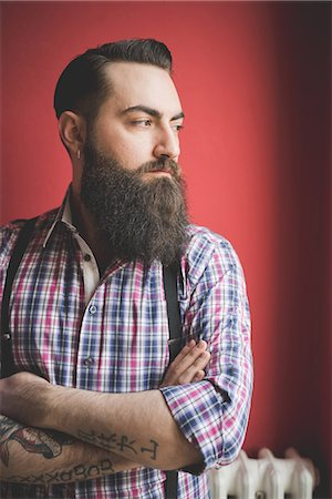 Portrait of young bearded man, red background Stock Photo - Premium Royalty-Free, Code: 649-08125289