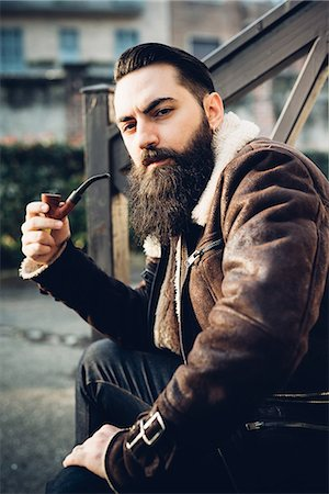 Young bearded man smoking pipe on steps Stock Photo - Premium Royalty-Free, Code: 649-08125310