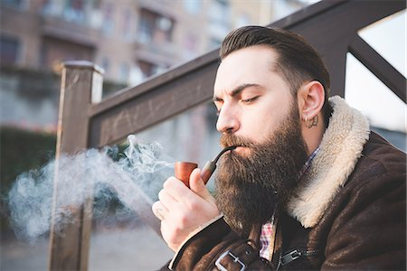 Young bearded man smoking pipe on steps Stock Photo - Premium Royalty-Free, Code: 649-08125311