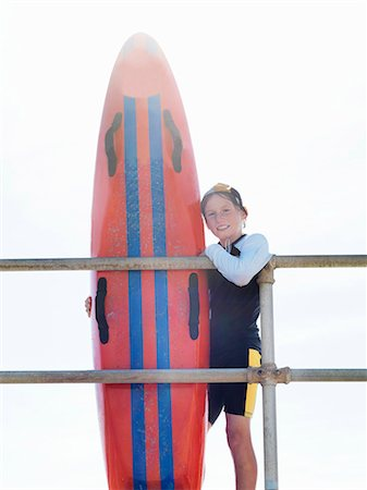 Portrait of boy nipper (child surf life savers) leaning against railings, Altona, Melbourne, Australia Stock Photo - Premium Royalty-Free, Code: 649-08125345