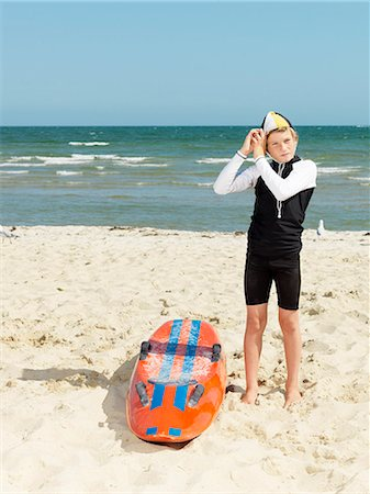 Portrait of boy nipper (child surf life savers) putting on cap, Altona, Melbourne, Australia Stock Photo - Premium Royalty-Free, Code: 649-08125349