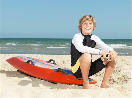 Portrait of confident boy nipper (child surf life savers) sitting on surfboard, Altona, Melbourne, Australia Stock Photo - Premium Royalty-Free, Code: 649-08125350