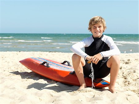 Portrait of confident boy nipper (child surf life savers) sitting on surfboard at beach, Altona, Melbourne, Australia Stock Photo - Premium Royalty-Free, Code: 649-08125351